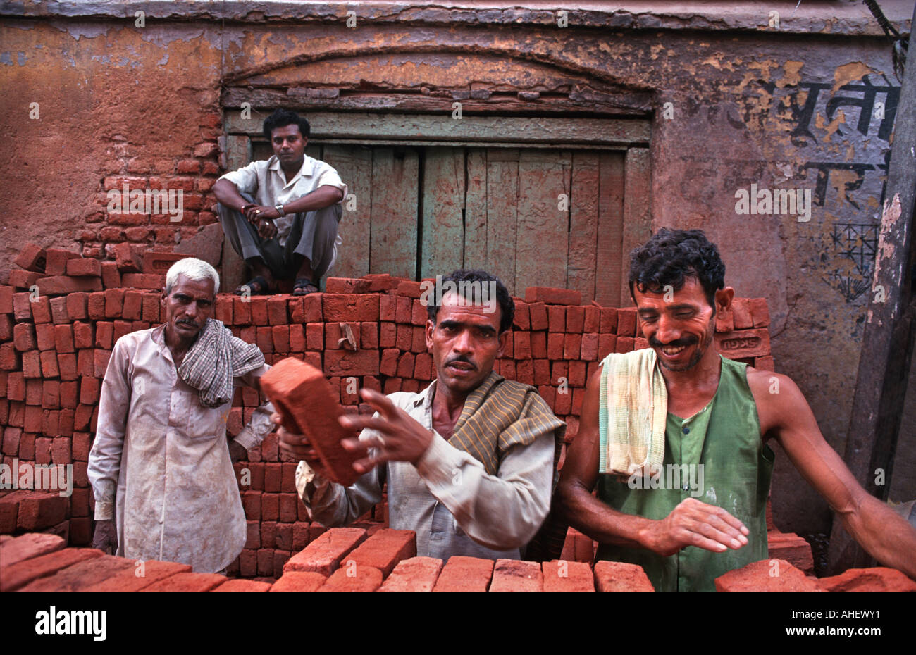 Busy Chandri Chowk area of central Delhi Bricklayers among stacks of bricks in the market area India - Stock Image