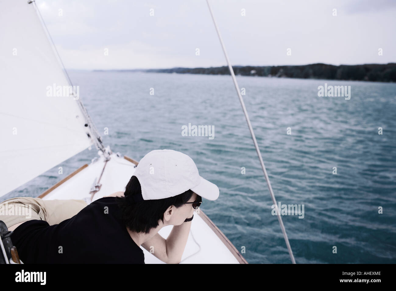 Young Woman Resting On Deck Of Sailboat - Stock Image