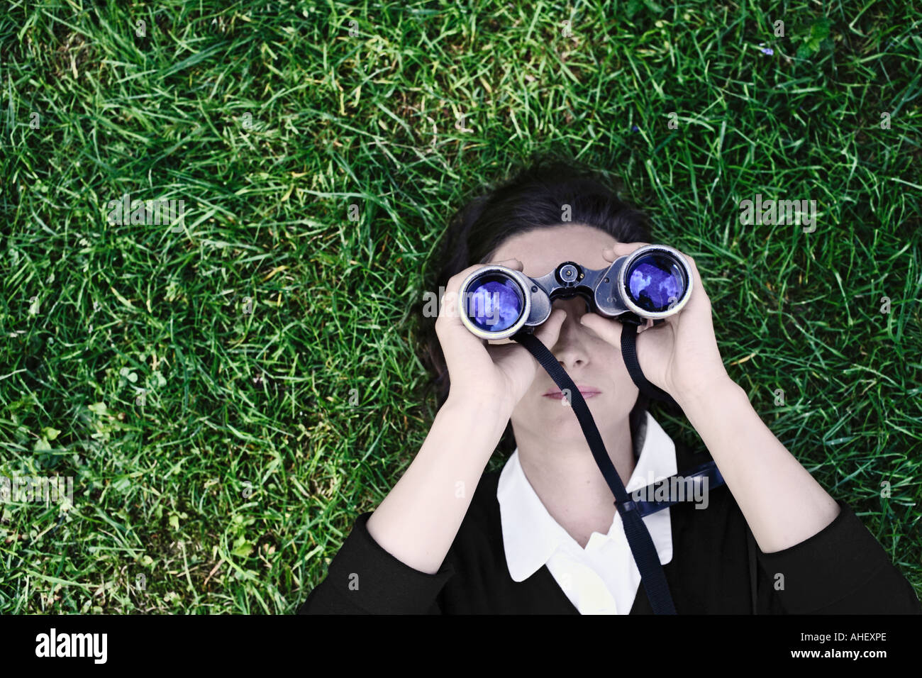 Woman Laying On Grass Looking Into Blue Sky Through Pair Of Field Glasses - Stock Image