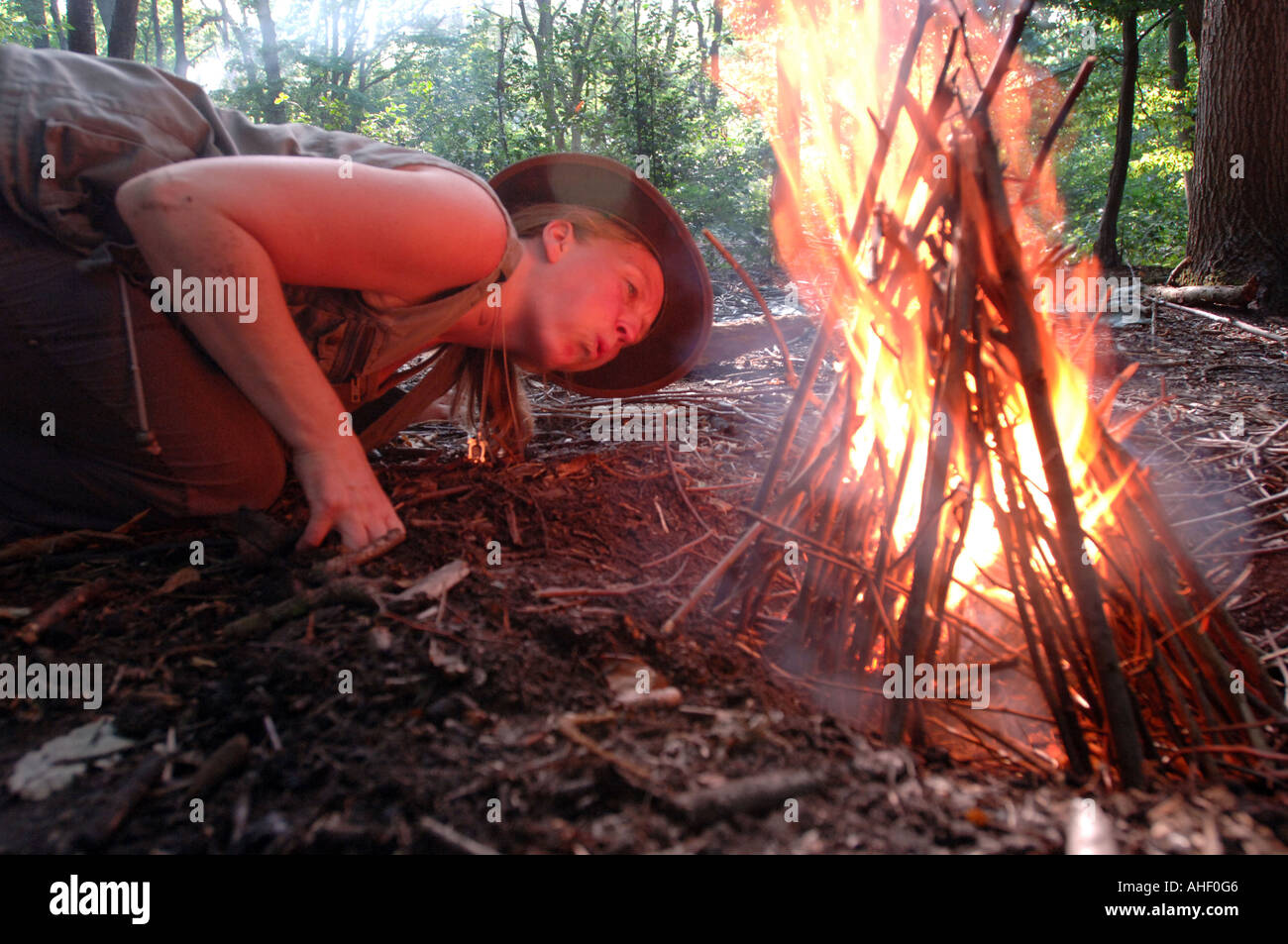 Woman wilderness expert demonstrates how to light a camp fire. - Stock Image