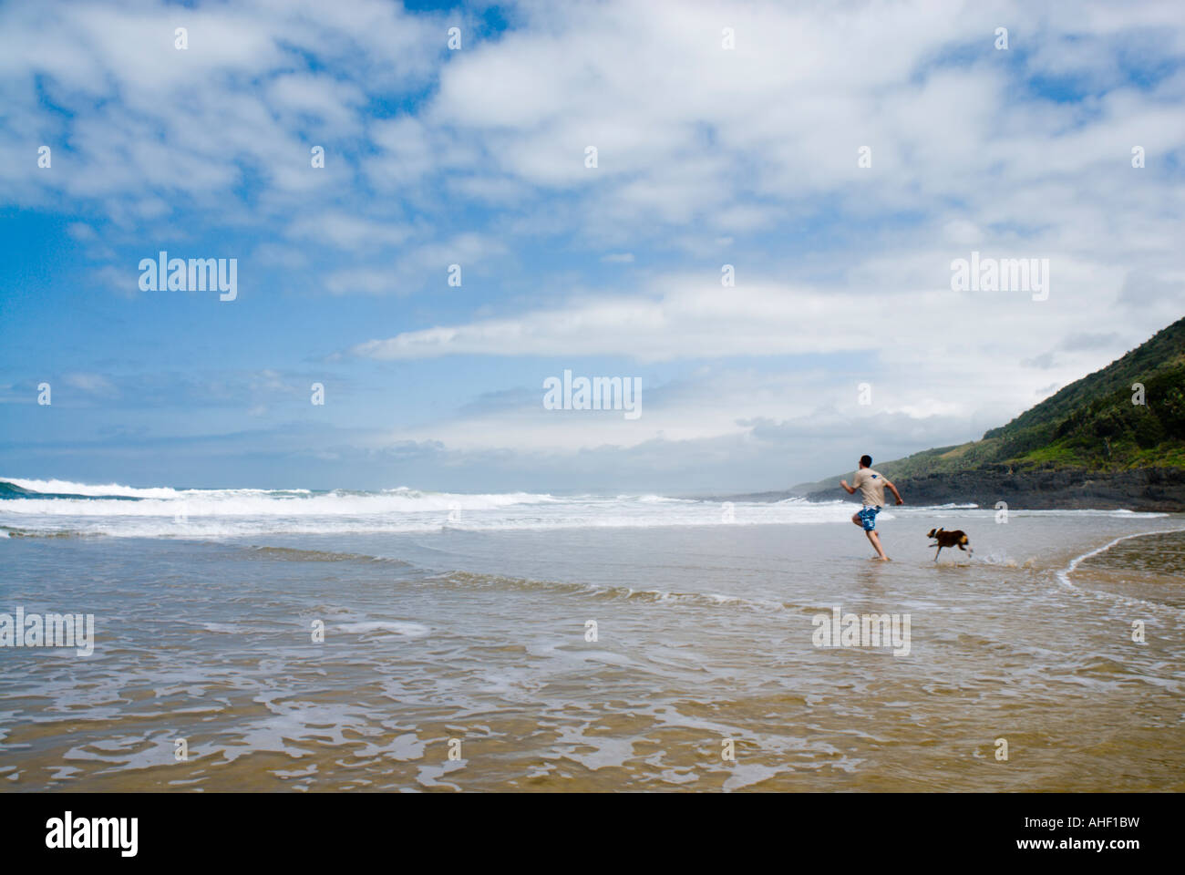 Male beach goer with dog at the seaside in Haga Haga, Eastern Cape, South Africa - Stock Image