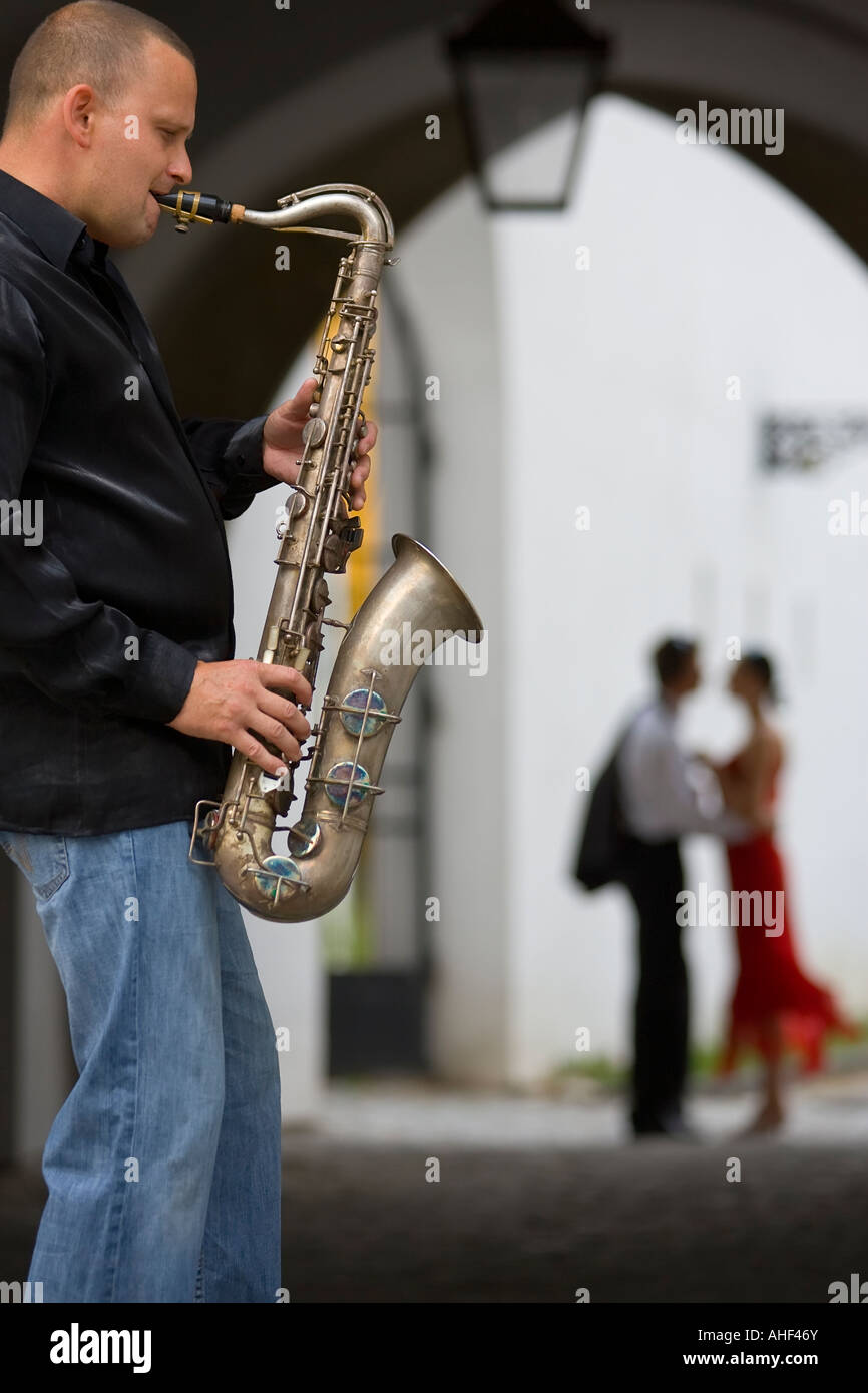 A street musician plays his saxophone while a romantic couple can be seen out of focus in the background - Stock Image