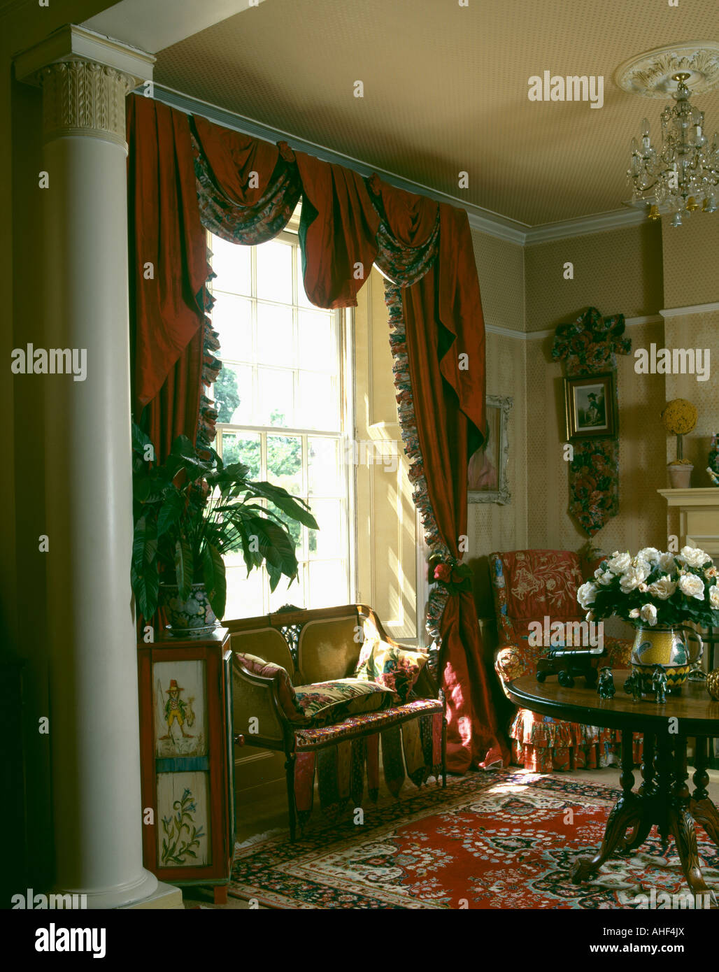 Swagged red curtains on window above small sofa in nineties ...