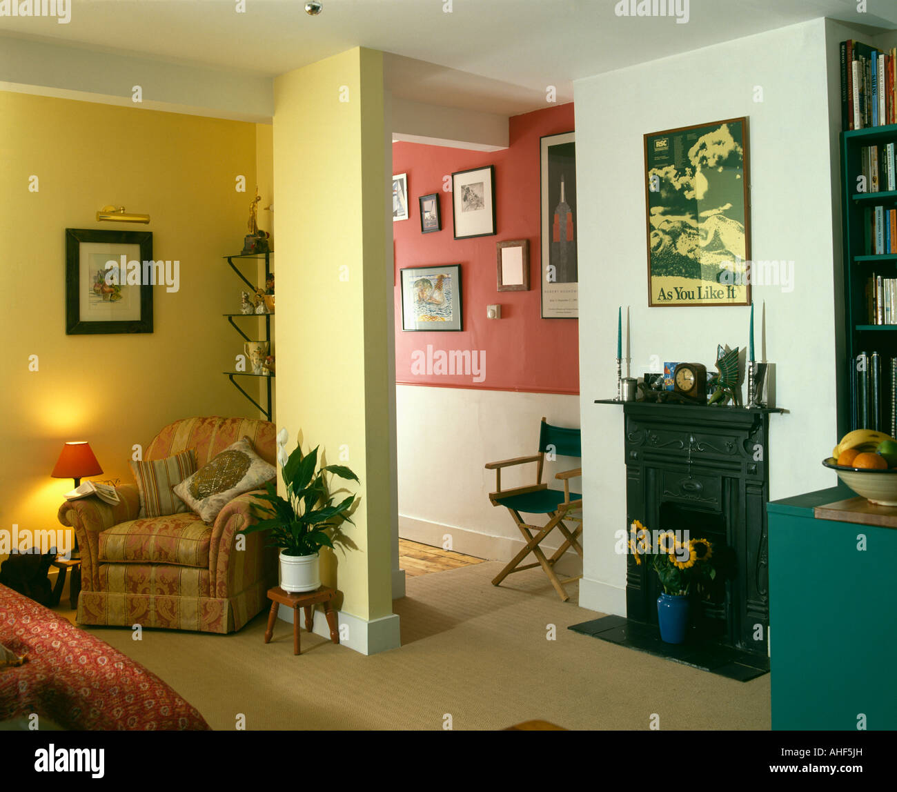 Armchair in corner of yellow sittingroom with fireplace beside doorway and view of red hall - Stock Image