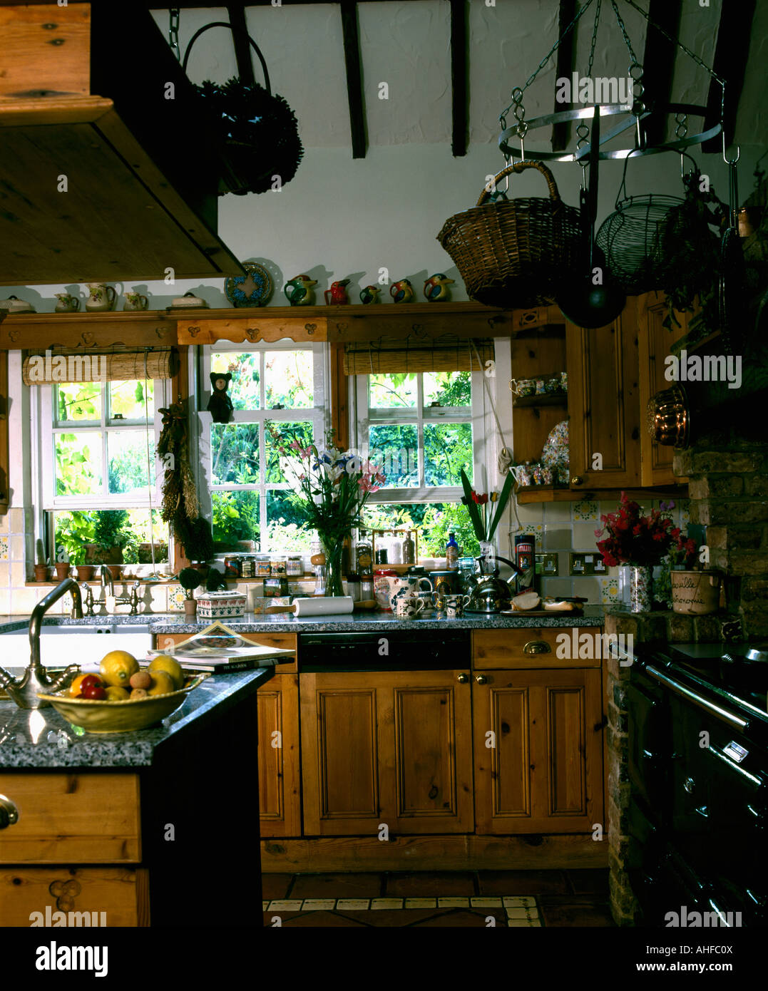 Wire and wicker baskets on hanging plate rack in small country kitchen with wooden units and black Aga & Wire and wicker baskets on hanging plate rack in small country Stock ...