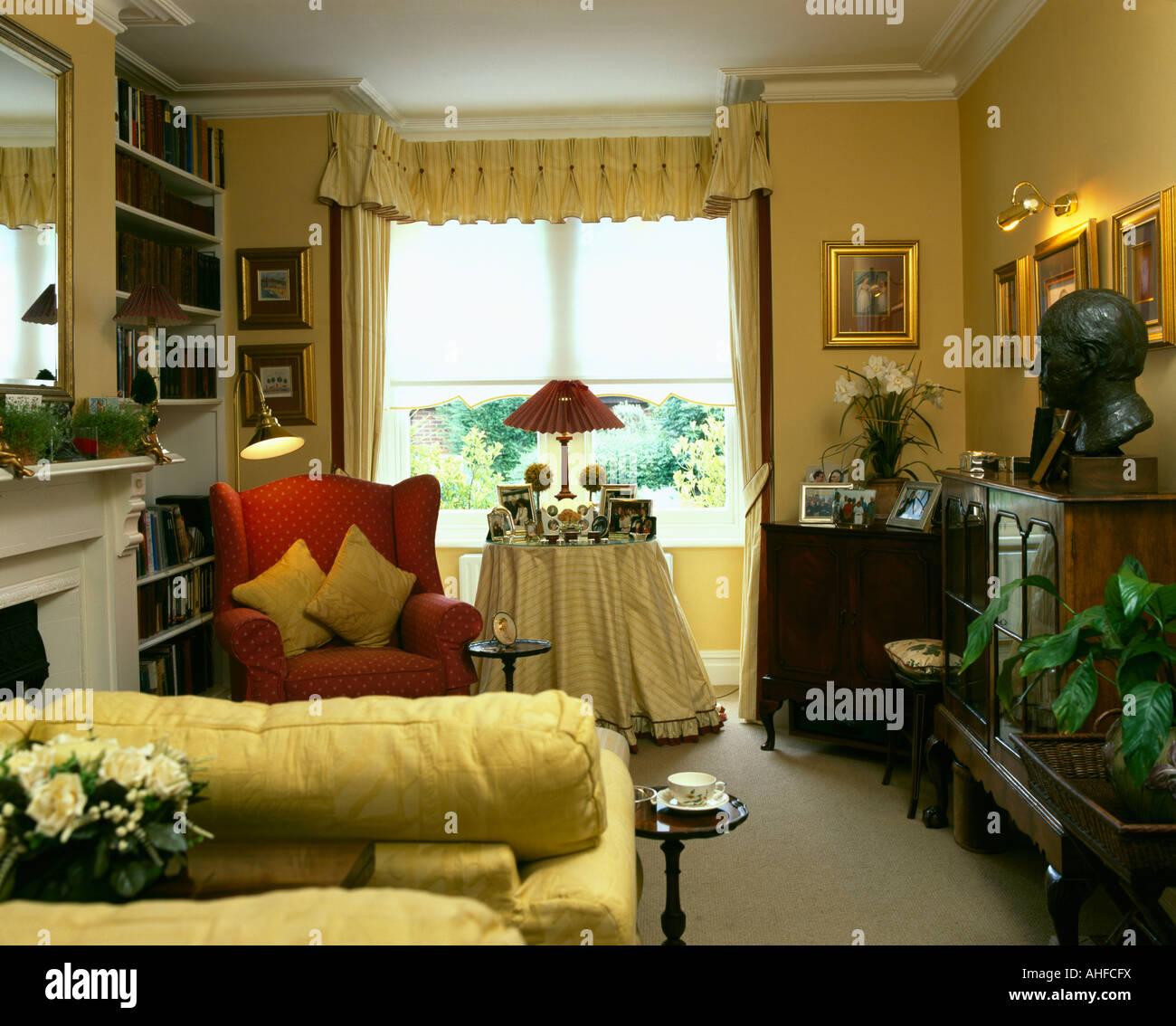 Yellow sofa & red armchair in yellow nineties living room with yellow curtains and yellow cloth on table in front Stock Photo