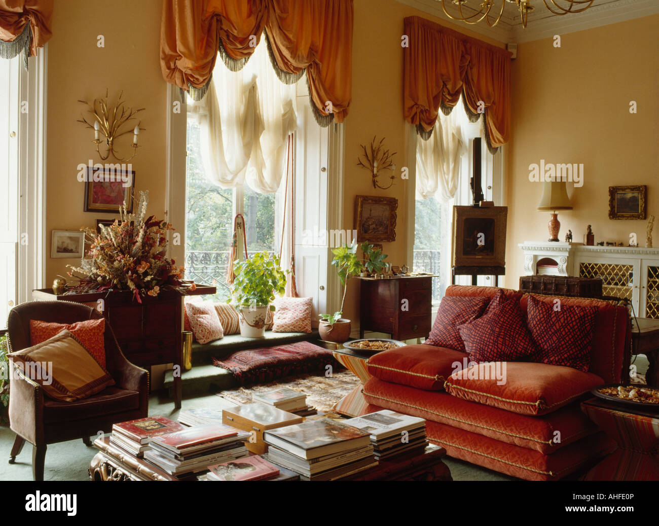 Armchair And Rust Velvet Sofa On Either Side Of Table Piled With Books In  Townhouse Living Room With Peach Ruched Blinds