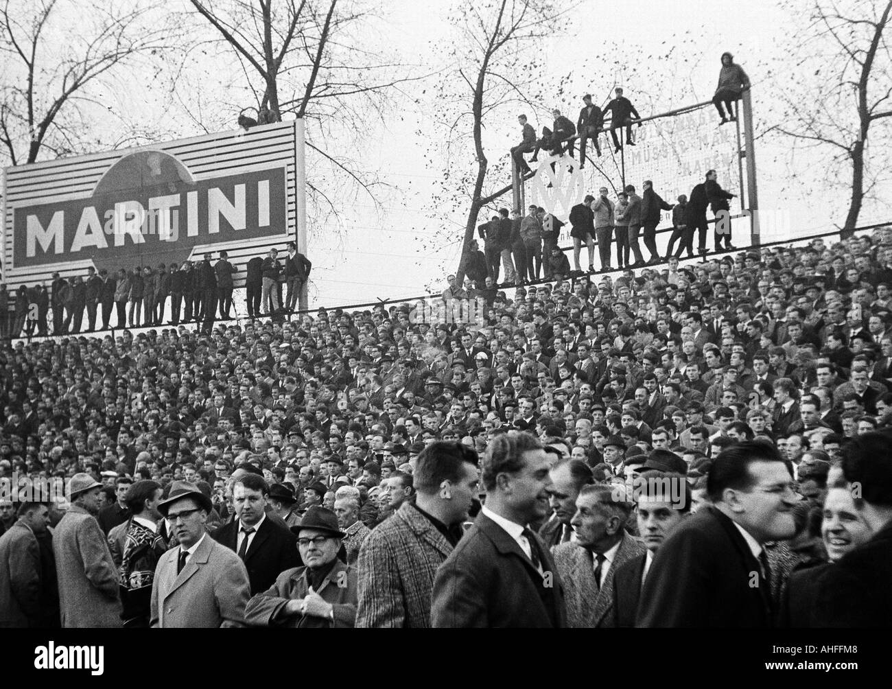football, Bundesliga, 1965/1966, FC Schalke 04 versus FC Bayern Munich 1:1, Glueckaufkampfbahn Stadium in Gelsenkirchen, crowd of spectators, football fans on a advertising billboard - Stock Image