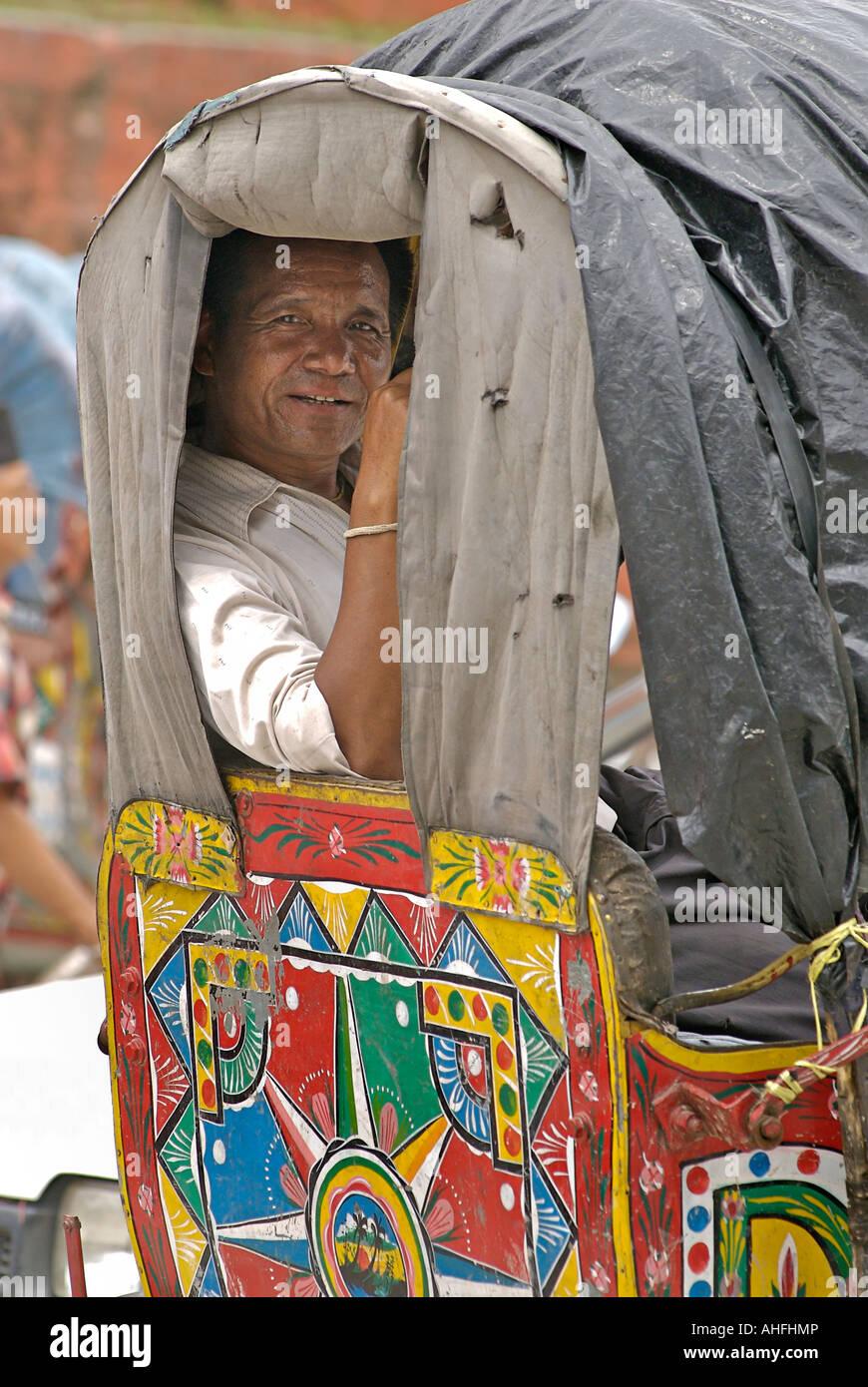 Portrait of a rickshaw driver sitting on the passenger seat Kathmandhu Nepal - Stock Image