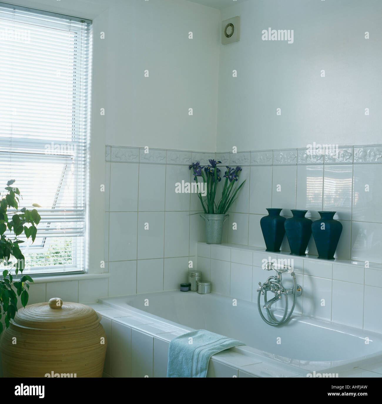 Row of pots on tiled shelf above bath in white bathroom with tiled ...