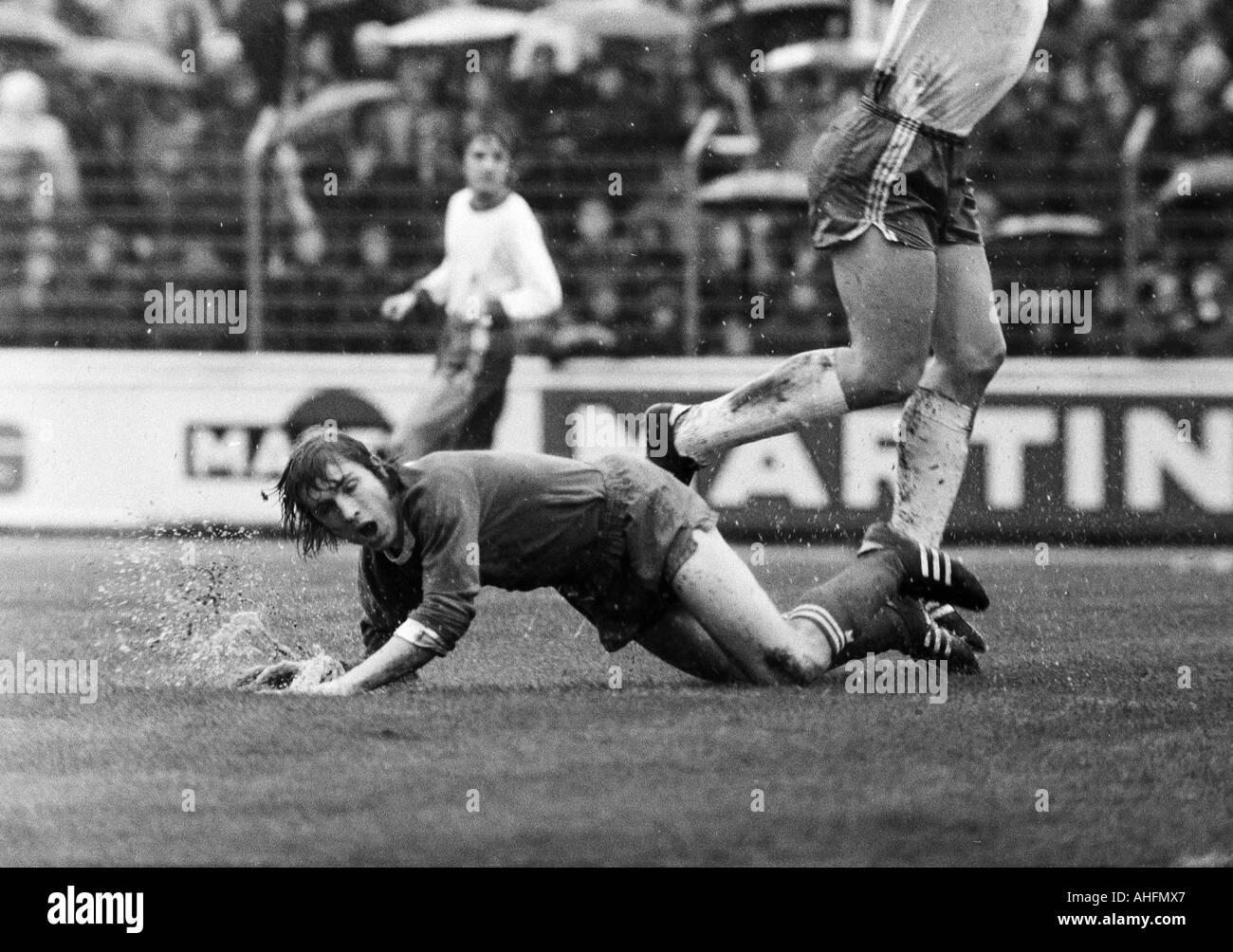 football, Bundesliga, 1971/1972, Niederrhein Stadium in Oberhausen, Rot-Weiss Oberhausen versus FC Schalke 04 2:3, rainy weather, game in heavy rain, scene of the match, Klaus Fischer (S04) aground - Stock Image