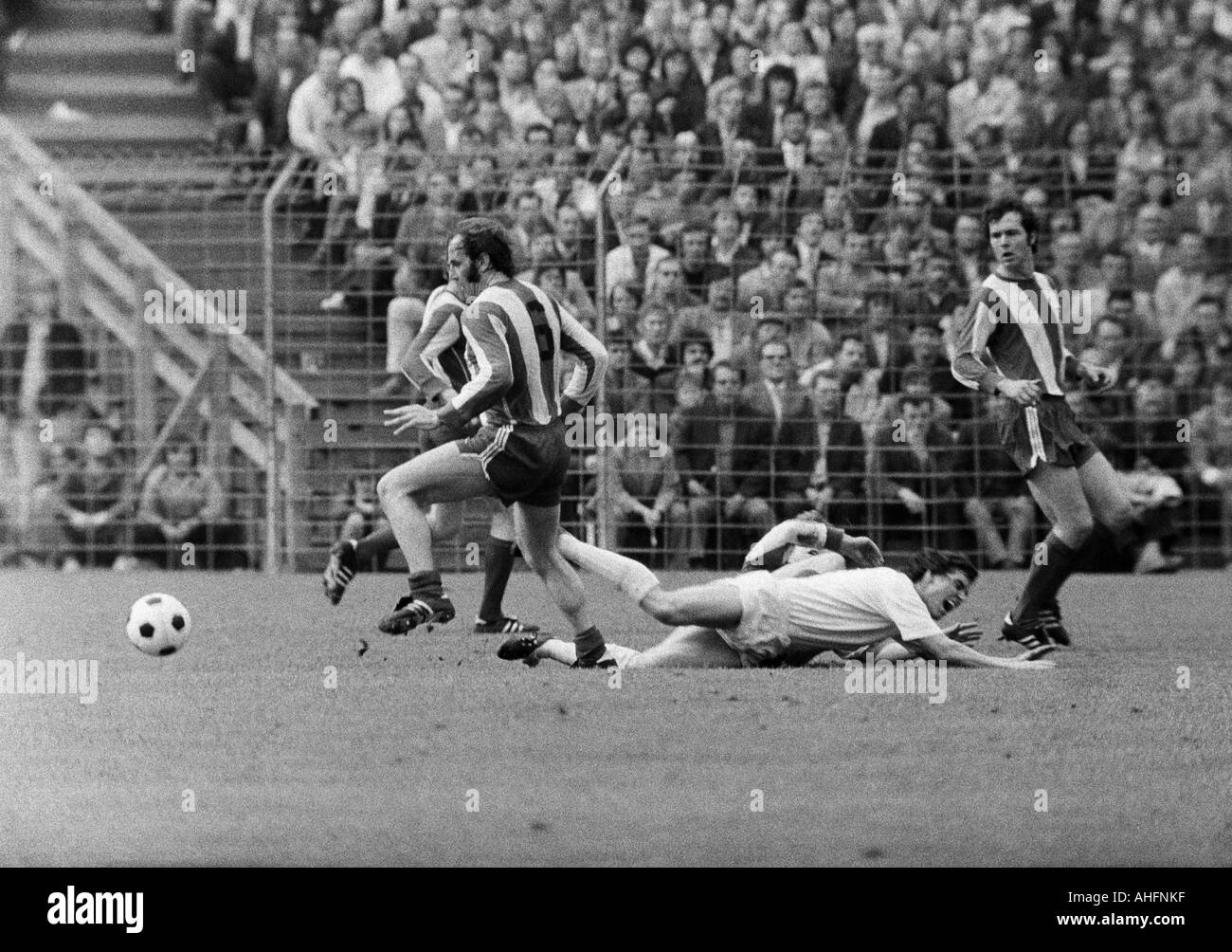 football, Bundesliga, 1971/1972, Stadium Radrennbahn near the Muengersdorfer Stadium in Cologne, 1. FC Cologne versus FC Bayern Munich 1:4, scene of the match, f.l.t.r. Franz Roth (FCB), Juergen Glowacz (Koeln) aground, Franz Beckenbauer (FCB) - Stock Image