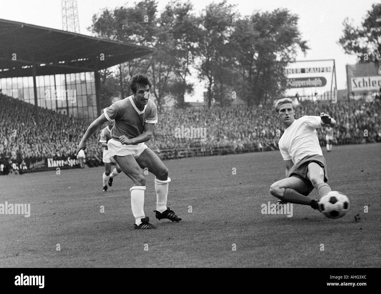 football, Bundesliga, 1967/1968, Glueckaufkampfbahn Stadium, Schalke 04 versus TSV 1860 Munich 0:0, scene of the match, Rudolf Brunnenmeier (1860) passing, right Klaus Fichtel (Schalke) - Stock Image