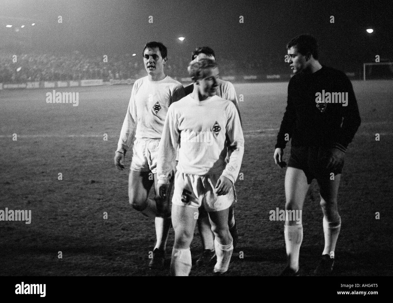 football, Bundesliga, 1967/1968, Muengersdorfer Stadium in Cologne, 1. FC Cologne versus Borussia Moenchengladbach 2:5, football players leaving the pitch, f.l.t.r. Peter Meyer, Berti Vogts, keeper Volker Danner (all MG) - Stock Image