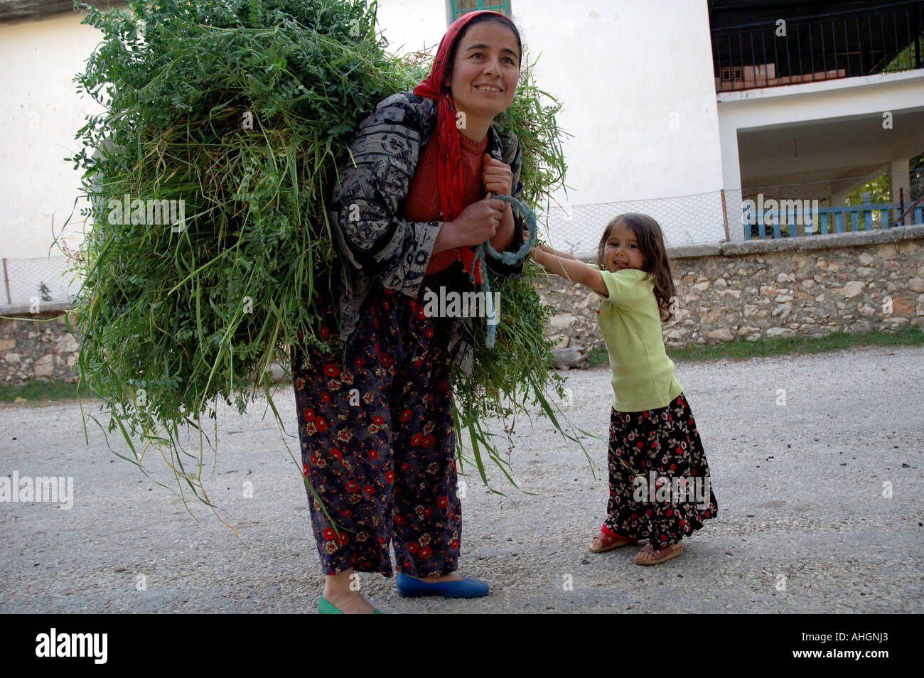 Mother and daughter carrying heavy load of grasses in small
