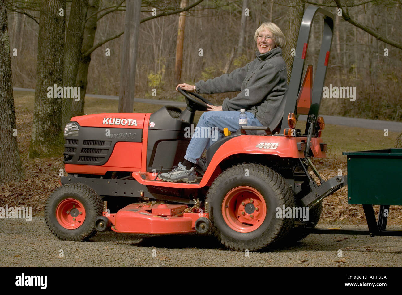 Mature woman landscaping her yard with a Kubota lawn tractor Stock ...