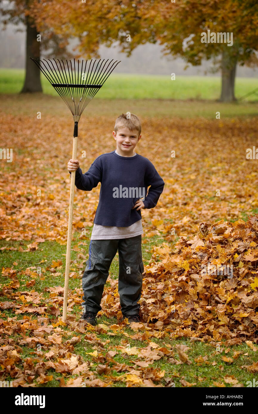 Boy 8 poses by a pile of leaves with a rake - Stock Image