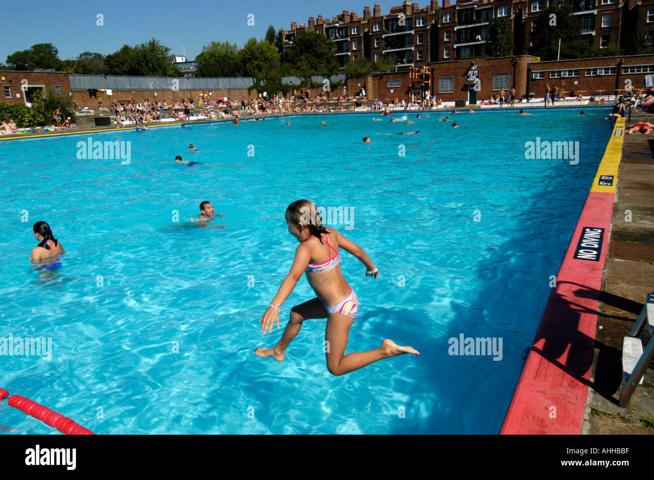 Young Girl Jumping Into The Water At The Lido Outdoor