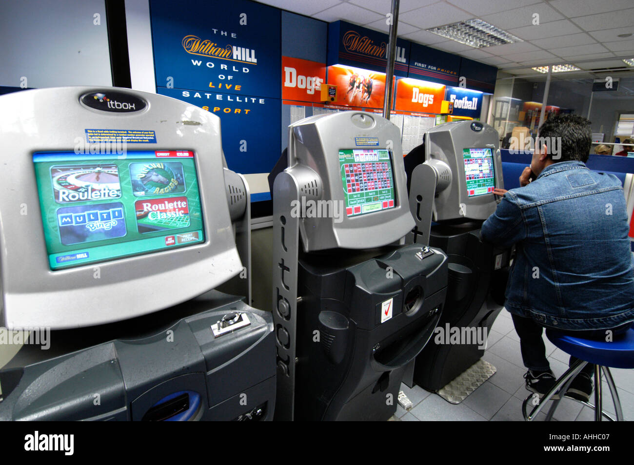 People playing roulette on fixed odds betting terminals at William Hill bookmakers, England, UK - Stock Image