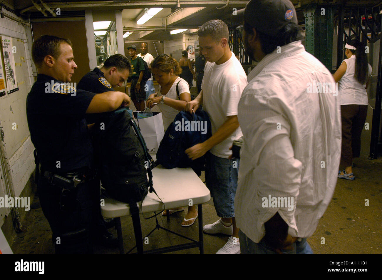NYPD officers perform random checks on commuters bags at the West Fourth Street subway station in Greenwich Village Since the bombings in London police have instituted inspections under strict guidelines so as to insure the checks are random and no profiling occurs - Stock Image