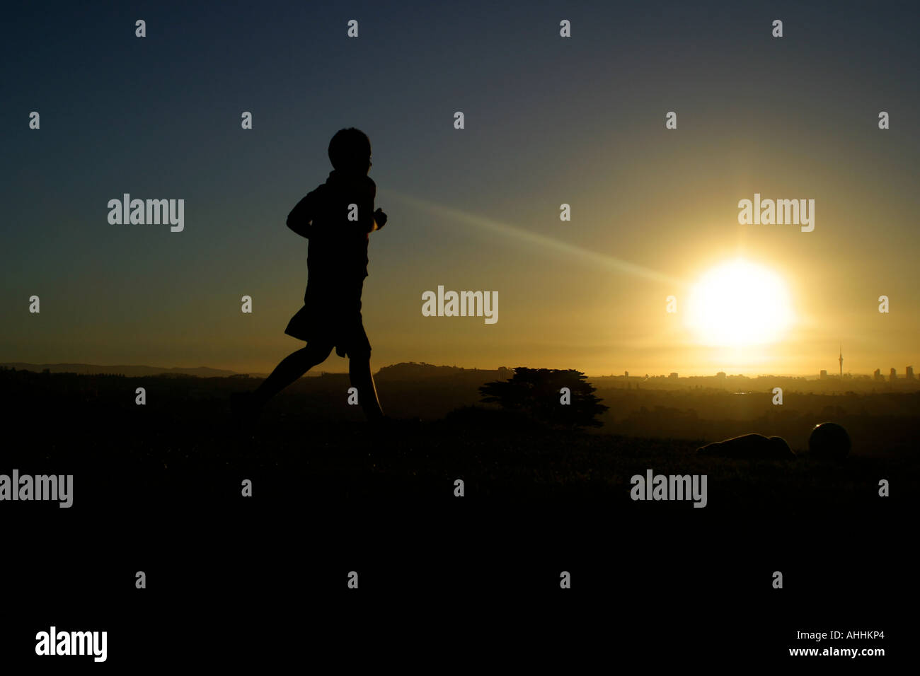 Boy playing soccer in Auckland New Zealand at Sunset - Stock Image