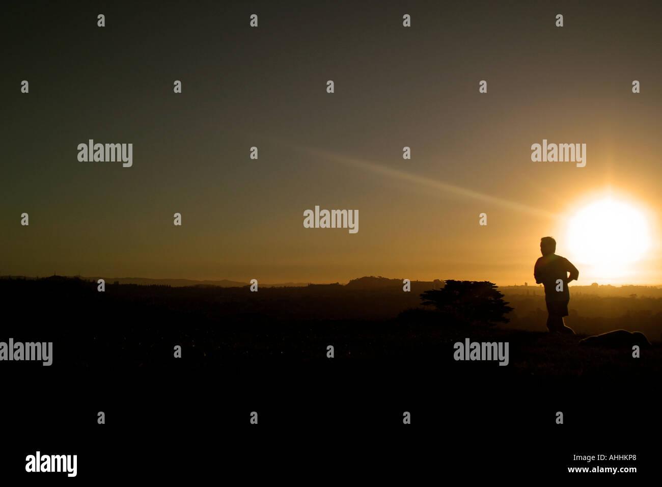 Man jogging at sunset - Stock Image
