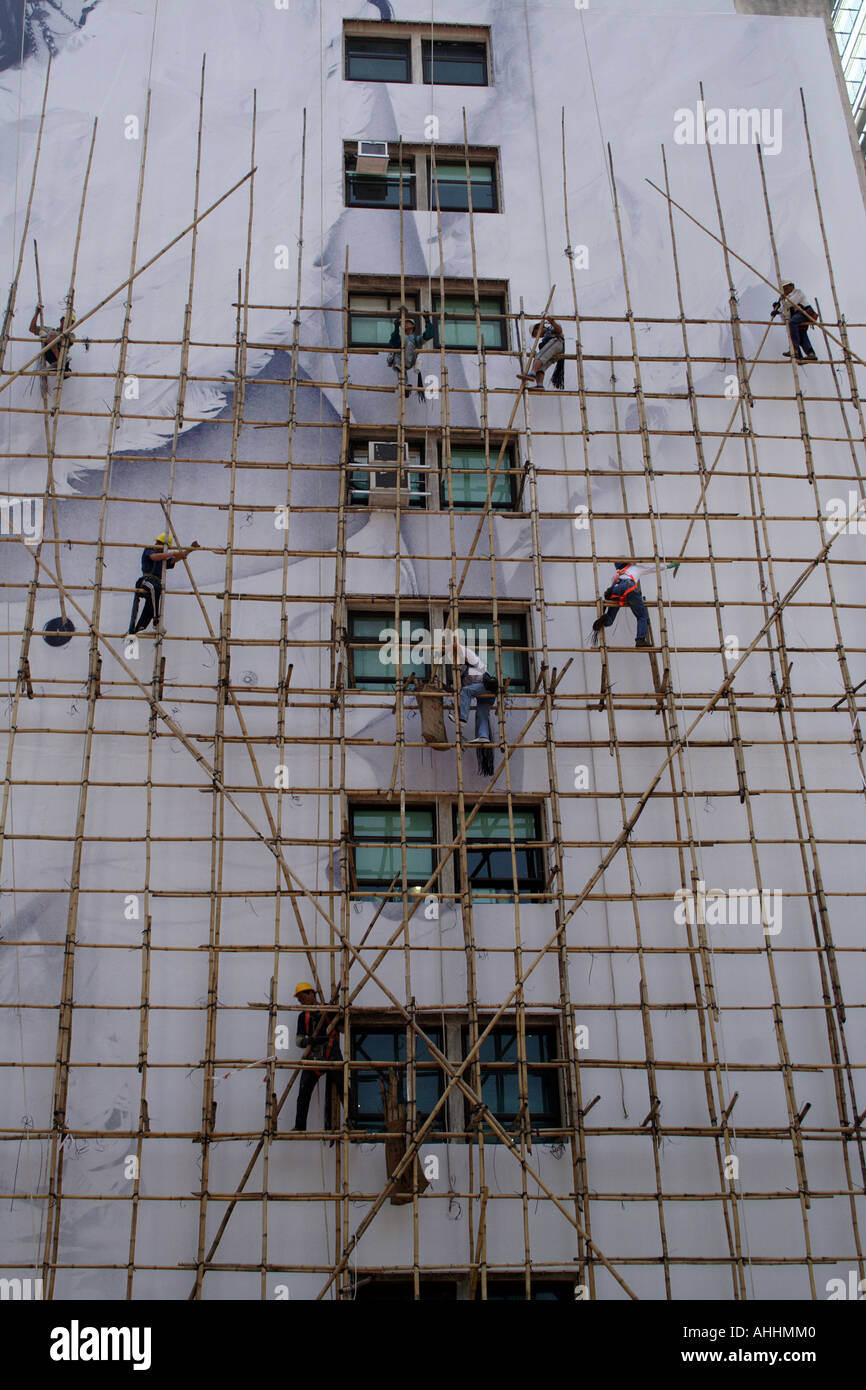Workmen on Bamboo Scaffolding on the Side of a Building, Hong Kong, China - Stock Image