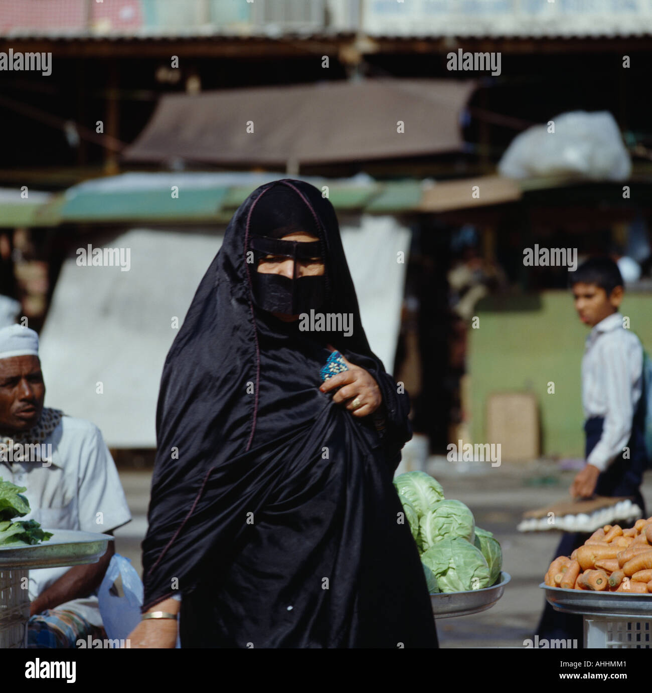 UAE Dubai Middle East Gulf State Arab woman in black clothing wearing yashmak covering her face at local street market. - Stock Image