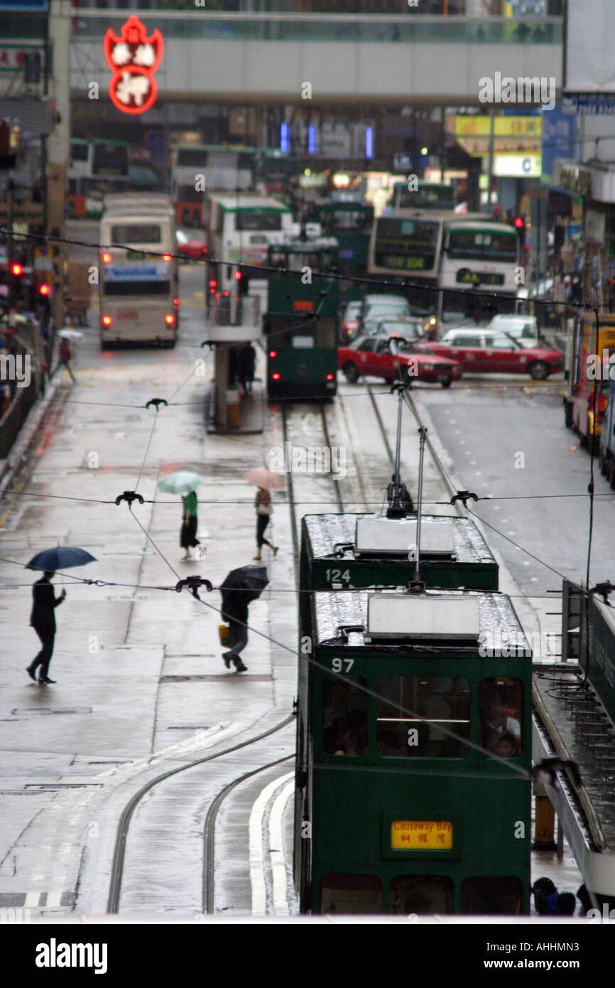 Trams and People Make their way through Central Downtown Hong Kong, China - Stock Image