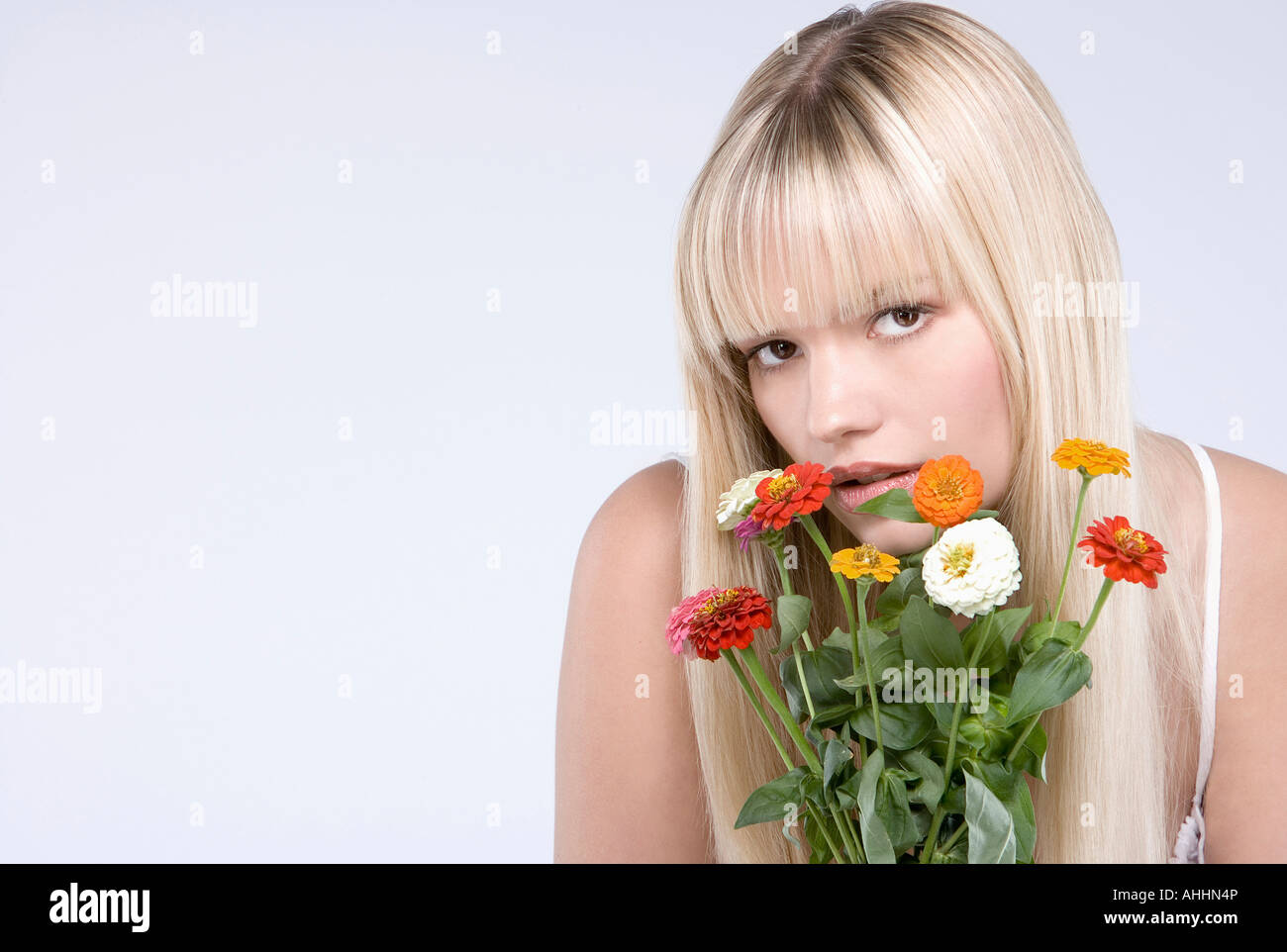 Young blond woman with a bunch of flowers - Stock Image