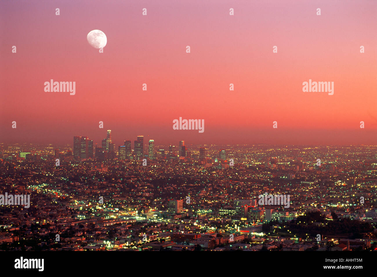 Los Angeles Civic Center amid urban sprawl under rising moon at dusk from Griffith Park Observatory - Stock Image