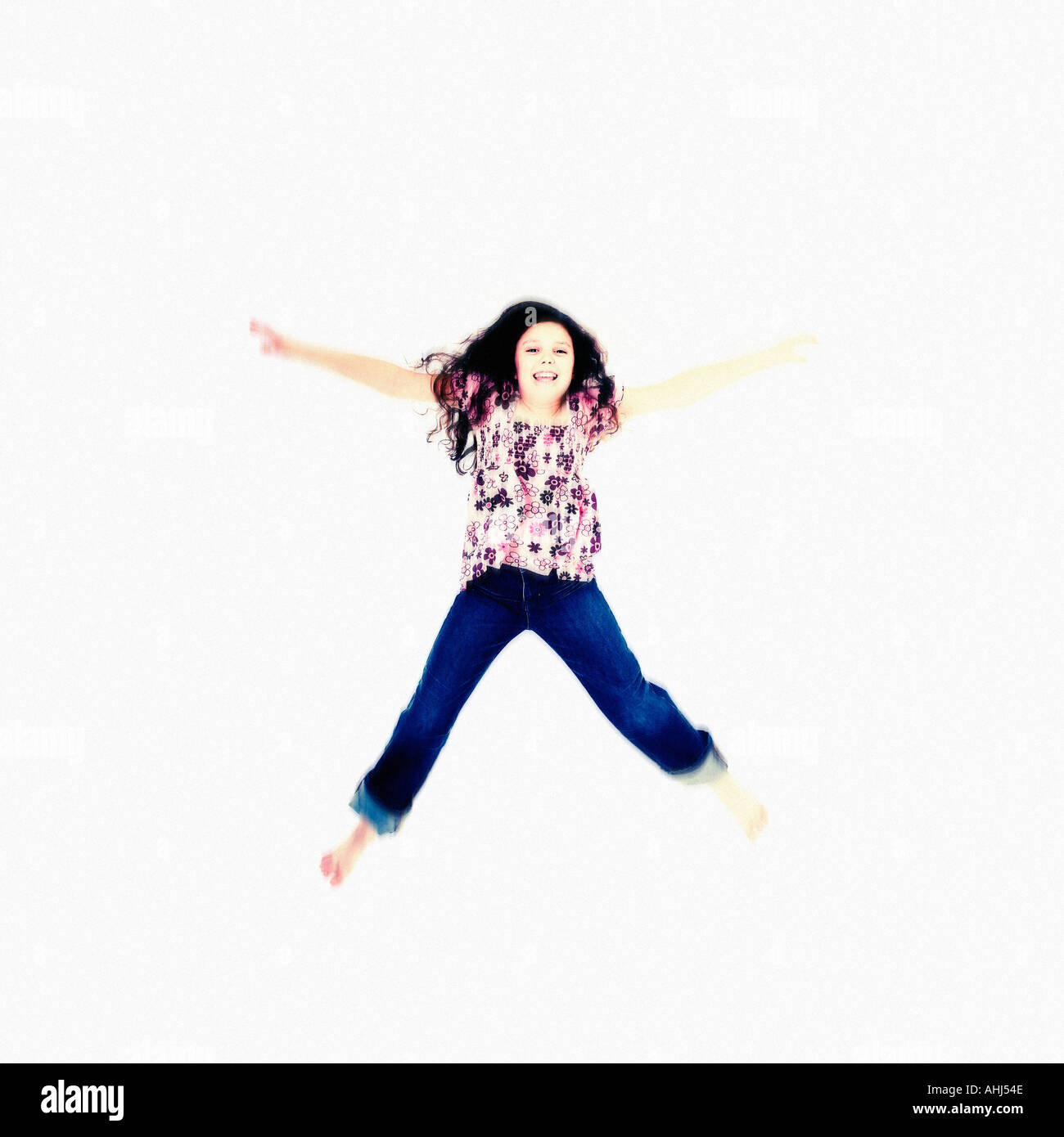 Girl doing star jump in air against white background - Stock Image