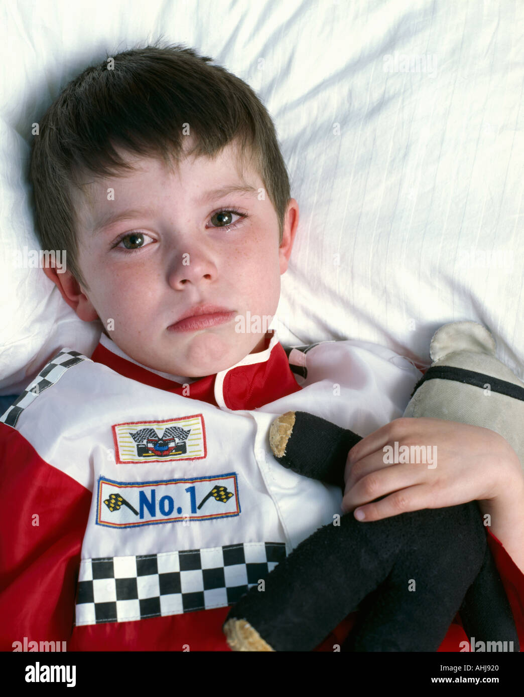 young boy 4 5 6 years old kid young male three four five six years old 3 4 5 6 close up cropped blue crying lying lie in bed bed - Stock Image