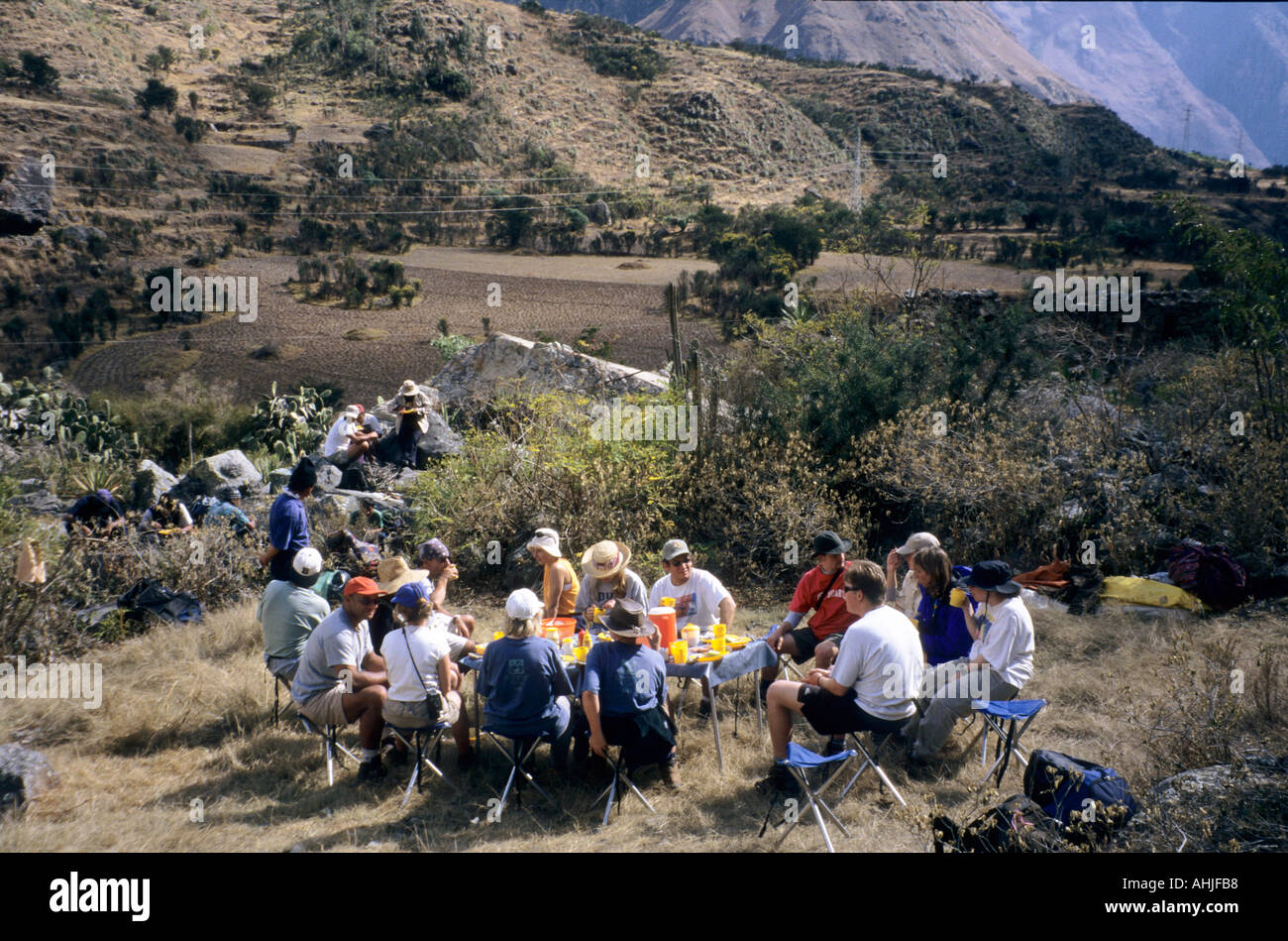 Group of tourists eating lunch at a folding table whilst guides and porters eat sitting on rocks behind. Inca Trail, Peru. Stock Photo