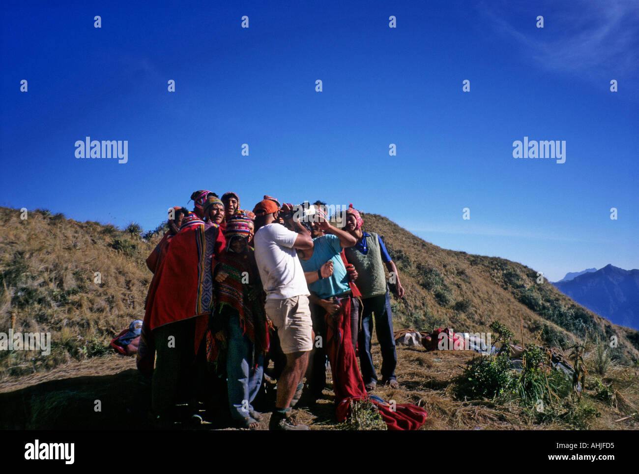 Inca Trail, Peru. Group of porters gathers around to watch playback on tourist videocamera at Phuyupatamarca campsite. - Stock Image