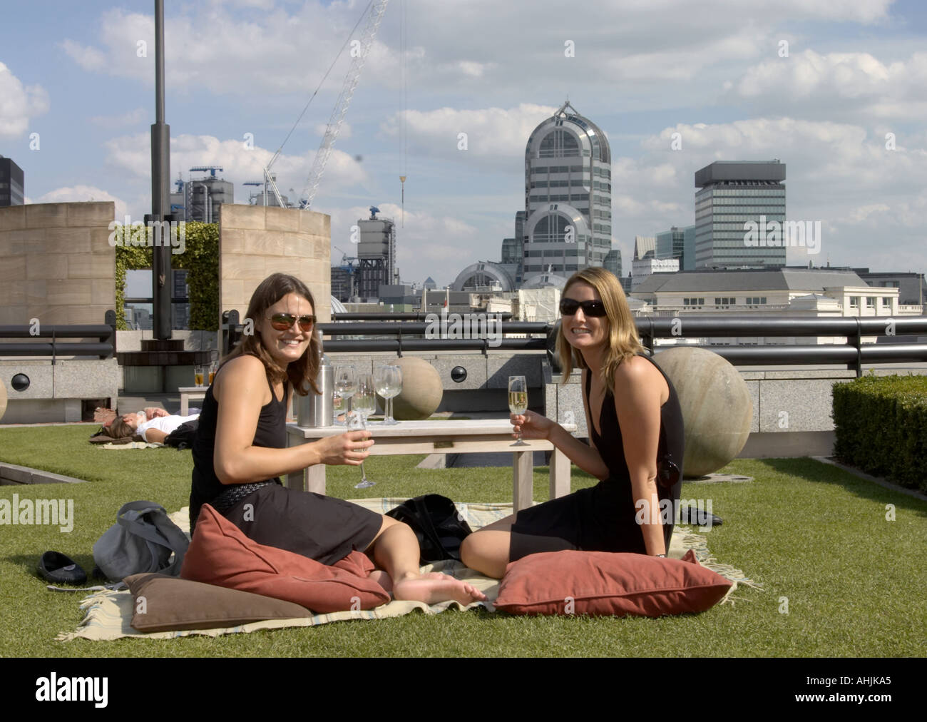 two young women enjoy wine at coq d'argent, no 1 poultry rooftop