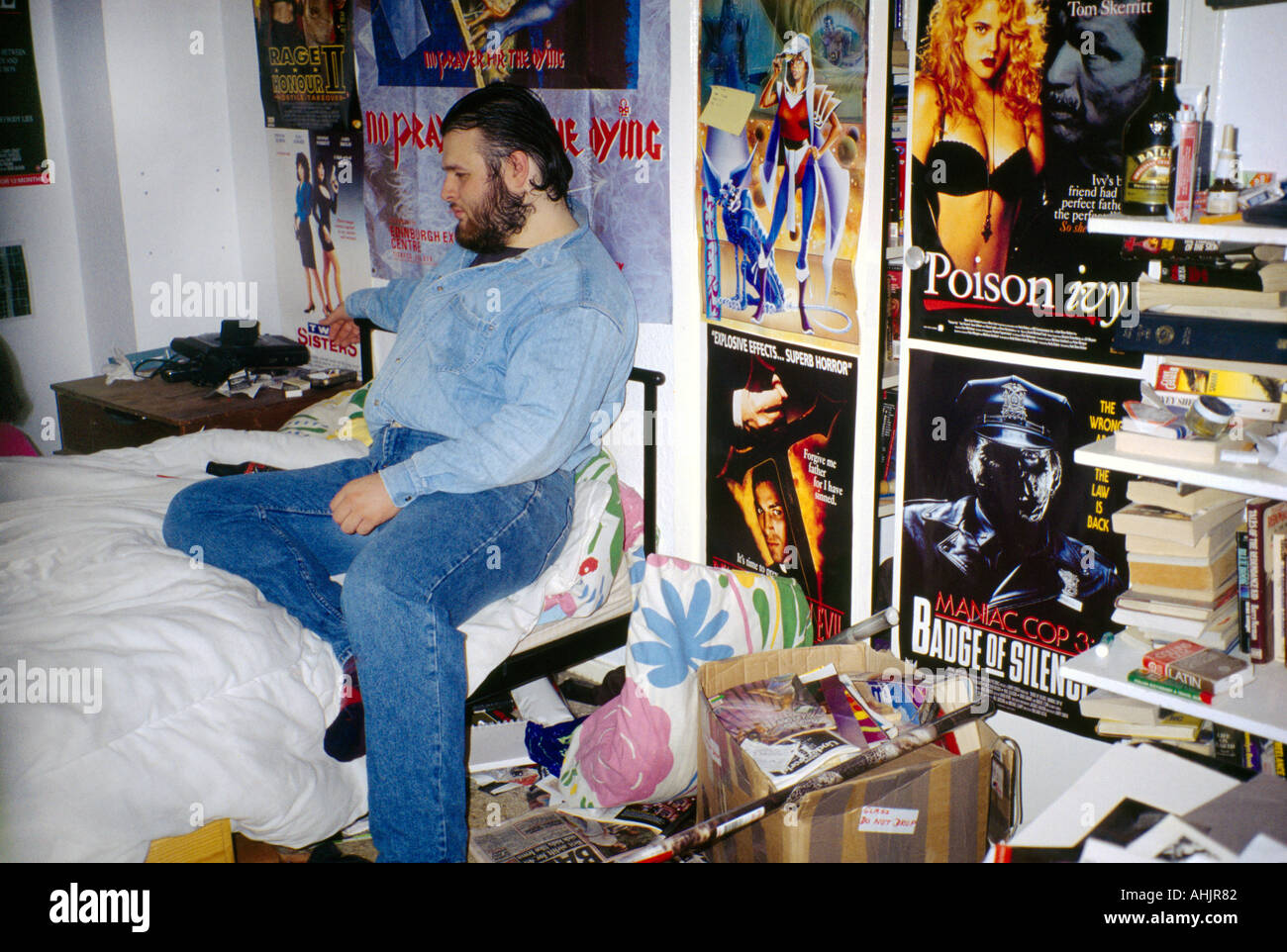 Teenager In Bedroom With Posters On Wall England Stock Photo