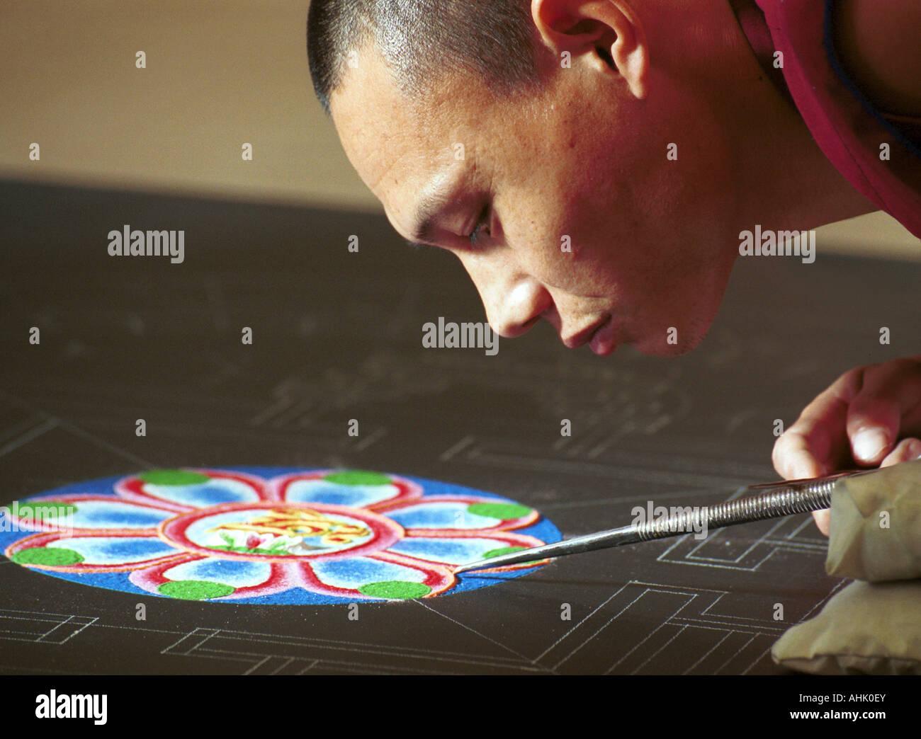 Tibetan monk working on a mandala sand mural - Stock Image