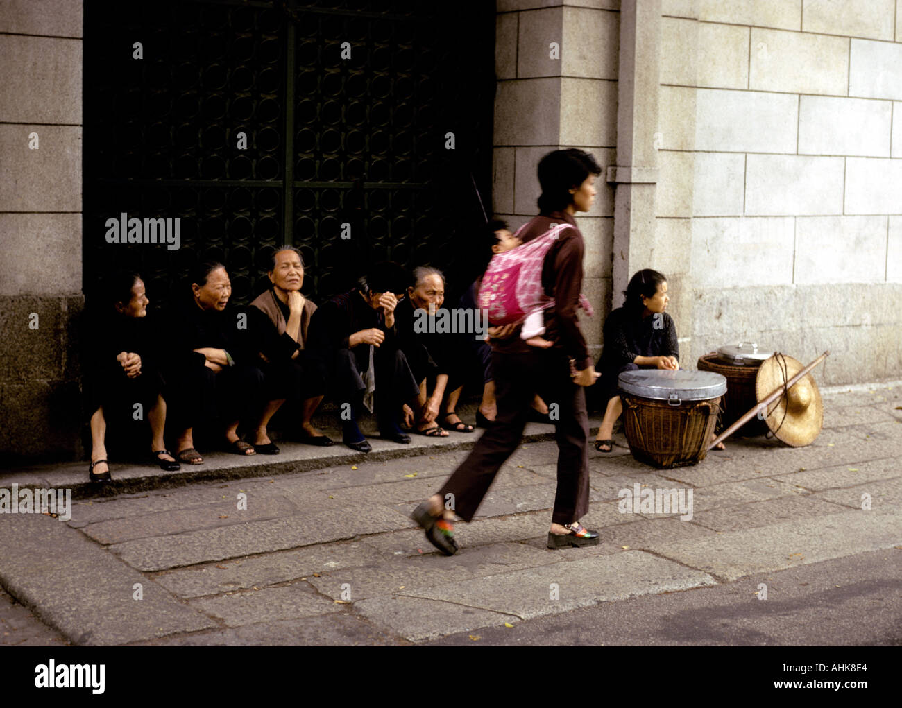 Seated women in black  in a doorway  watch the world go by Macao - Stock Image