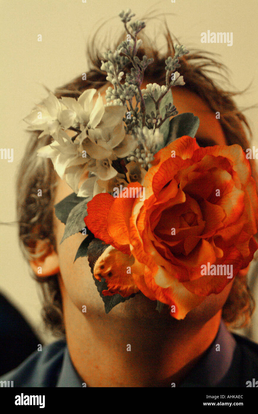 Young mans face coverd by artifical flowers - Stock Image