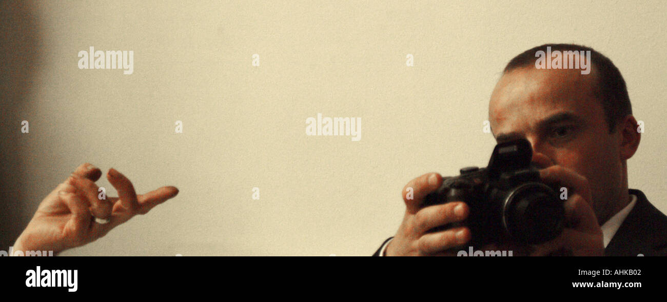 Young man staring into camera with another camera and lone hand - Stock Image