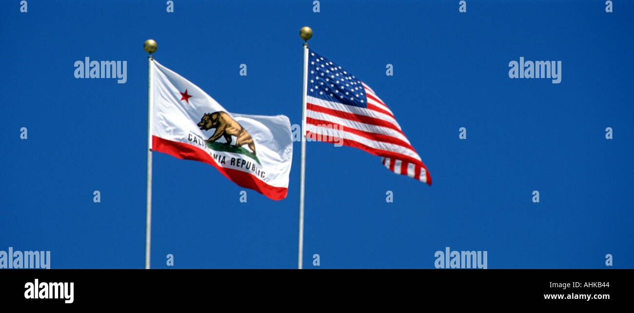 United States and California State flags flying against clear blue sky - Stock Image
