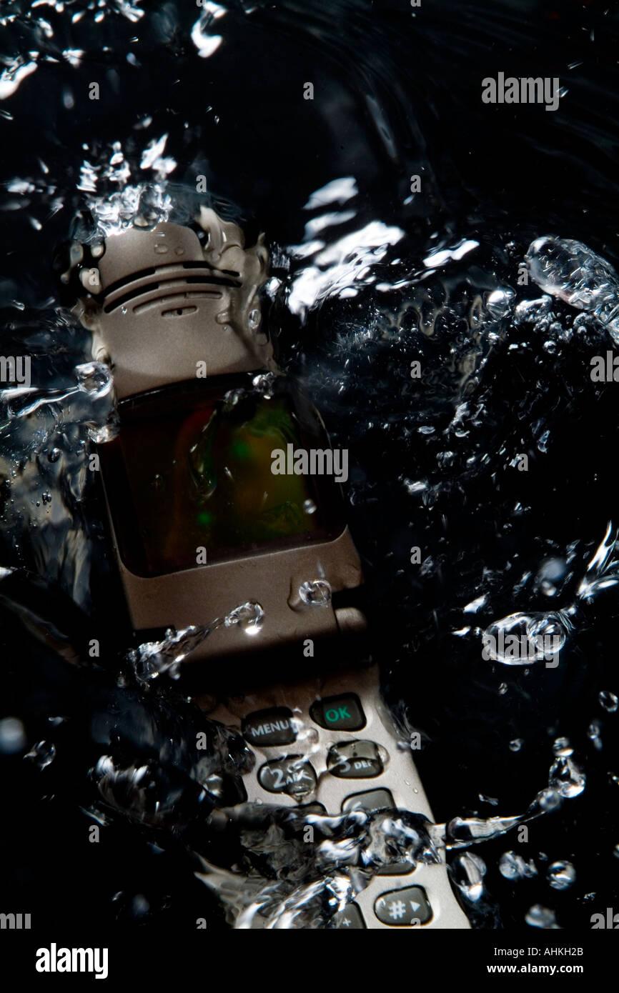 Action shot of cellular telephone splashing into water pool - Stock Image