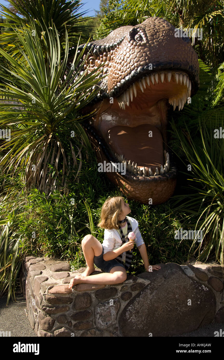 young girl eating icecream by Dinosaurs at Dan yr Ogof national showcaves of Wales Brecon Beacons National Park - Stock Image