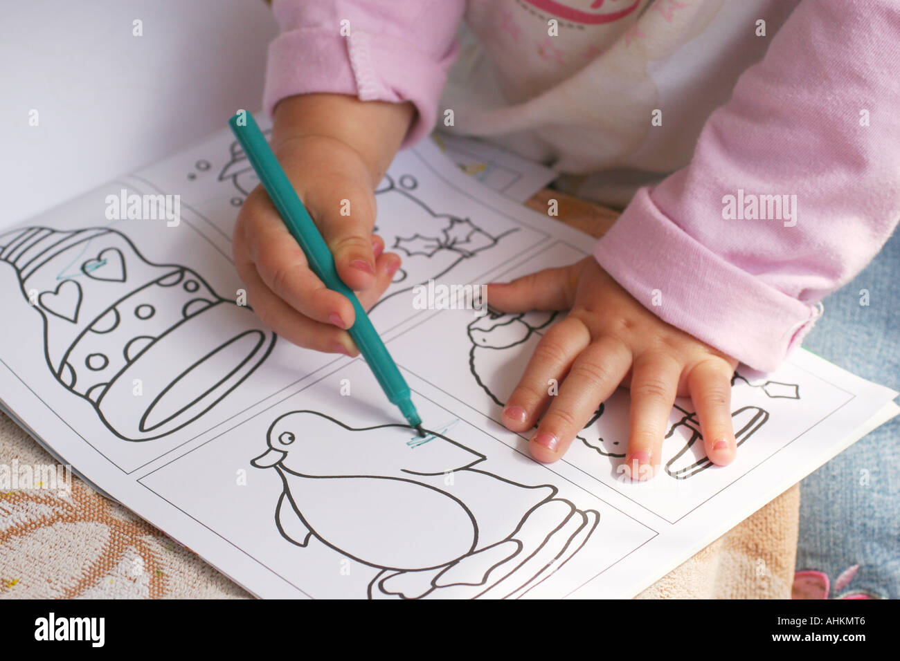 Close Shot Of Hands Very Young Child Drawing In A Childs Colouring Book