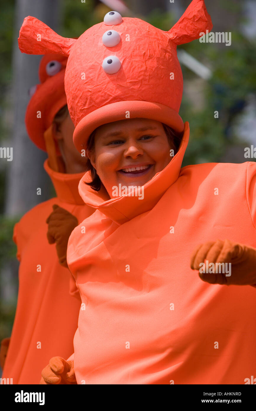Lady dressed as an orange alien and having fun on a carnival float - Stock Image