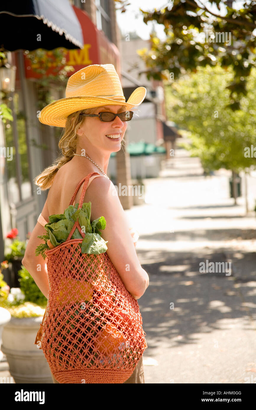 Woman carrying bag with vegetables - Stock Image