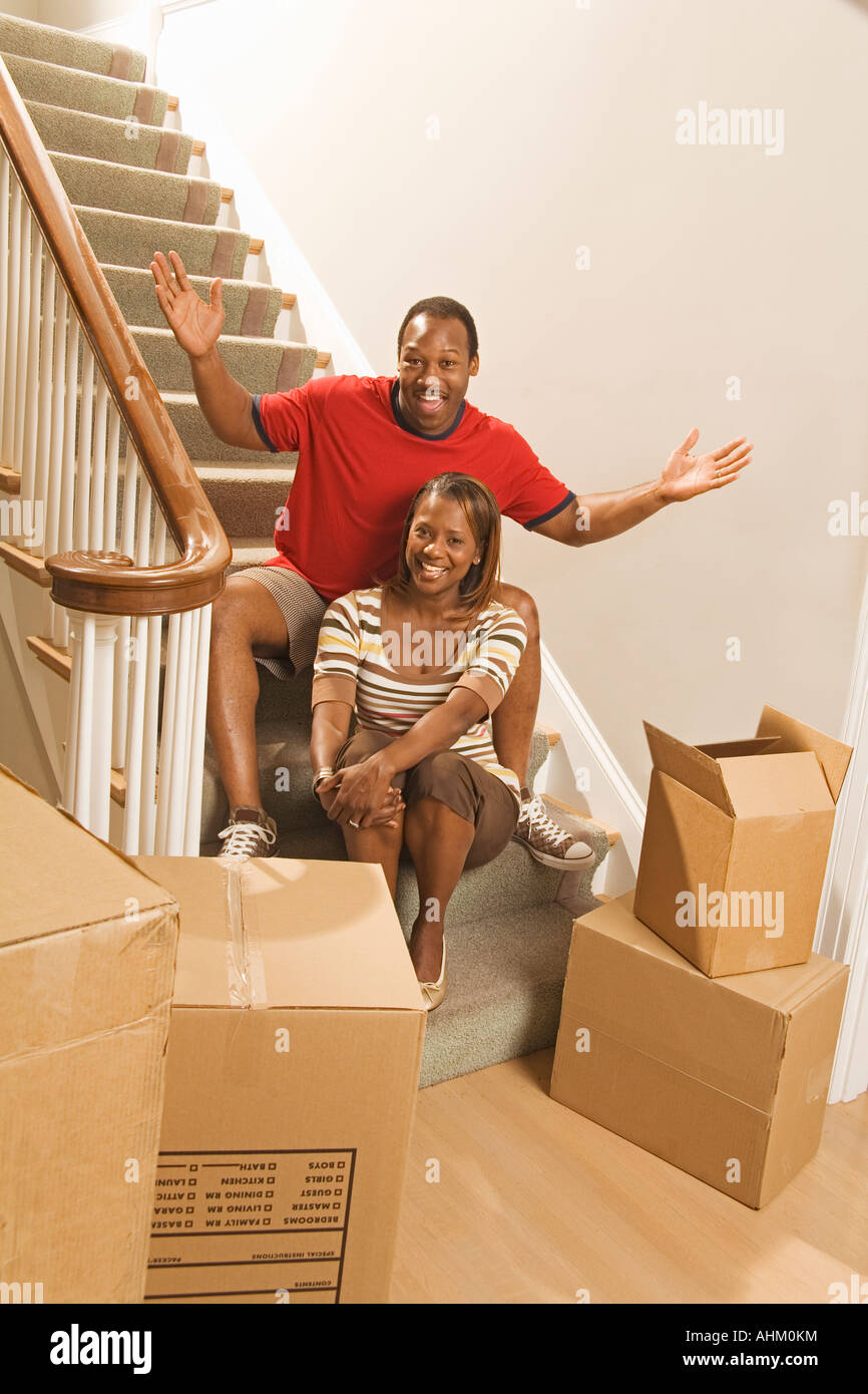African couple next to moving boxes - Stock Image