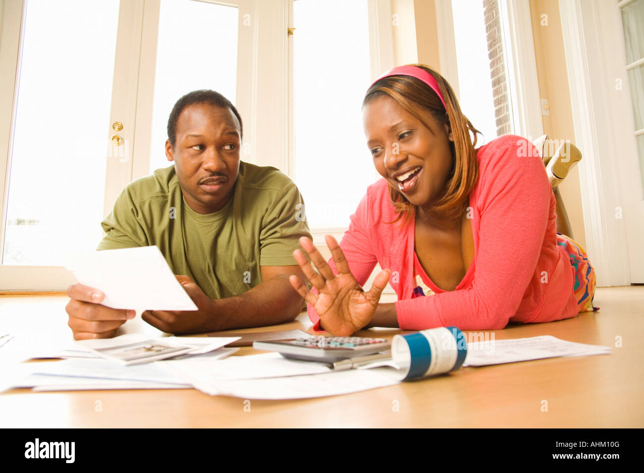 African couple paying bills in new house - Stock Image