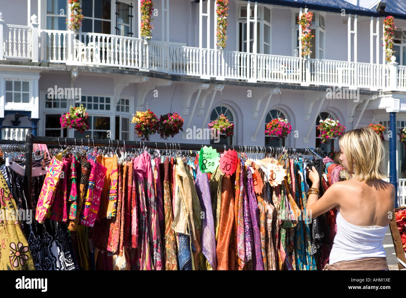 Woman looking at skirts at outdoor market Sidmouth Devon England - Stock Image